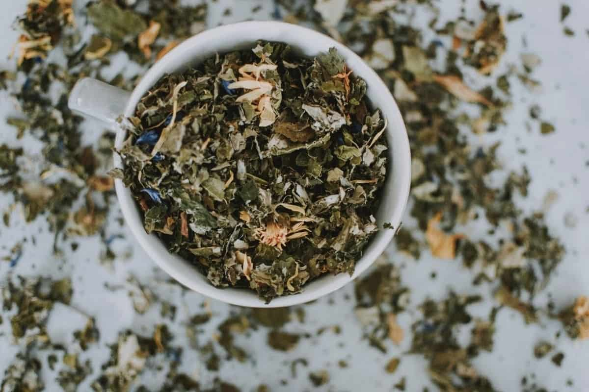 herbal teas in a cup out of a home apothecary cabinet