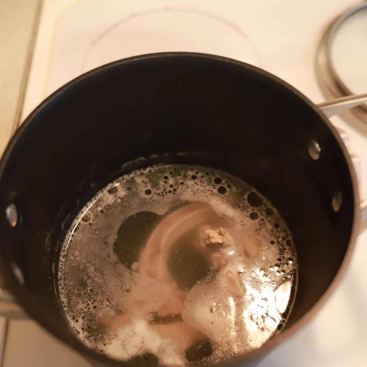 pork bone broth cooking on a stove