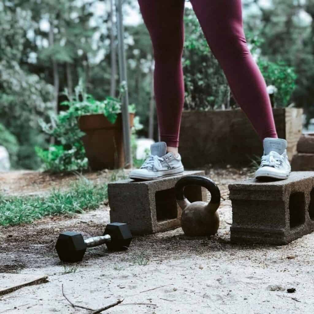 brianna nash standing on cinder blocks with her at-home gym equipment