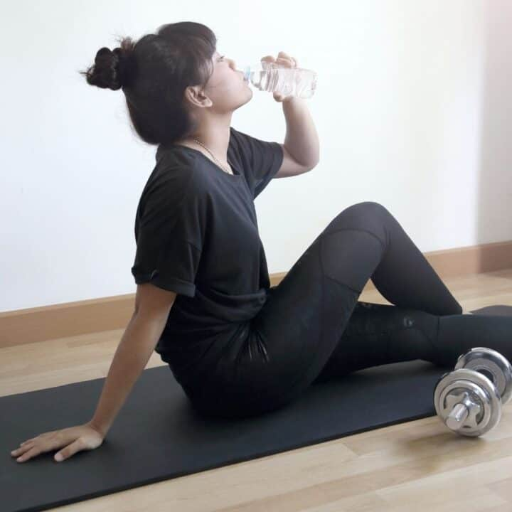 woman sitting on a yoga mat drinking water
