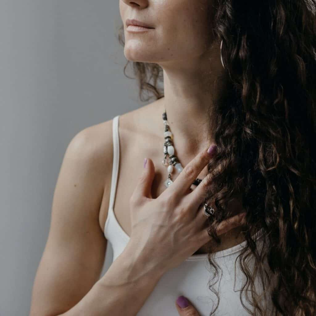 woman with her hands over her heart and stomach