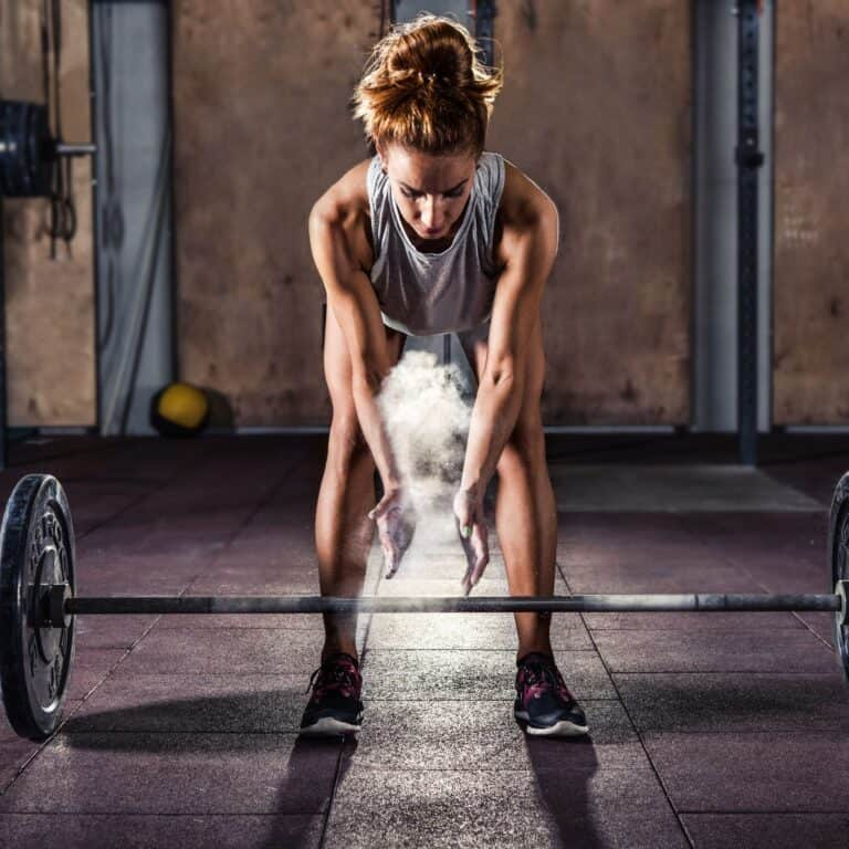 woman clapping chalk off her hands before lifting a barbell